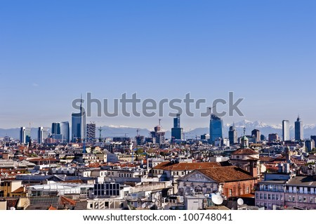 New panoramic skyline in Milan 2012. The picture was taken from the Duomo cathedral and shows the new buildings from the Garibaldi districts. The Alps, less than 50 miles away, are on the background. - stock photo