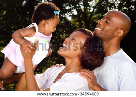 new parents posing with their infant daughter - stock photo
