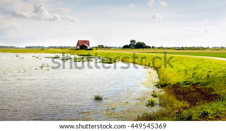 New polder area on a sunny day in the summer. In the foreground is a flooded field caused by the high water level in the river. On the dike on the background are new farms and outbuildings. - stock photo
