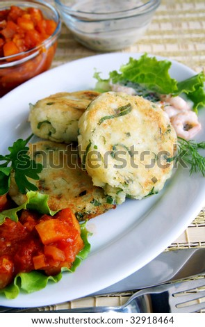 New potato and greens cakes with two sauces - apple-onion chatni and cream with shrimps, on a white dish, cottage food style, vertical - stock photo