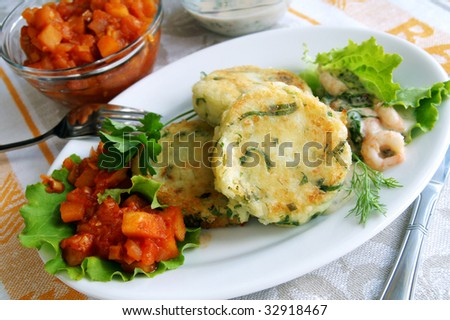 New potato and greens cakes with two sauces - apple-onion chatni and cream with shrimps, on a white dish, cottage food style - stock photo