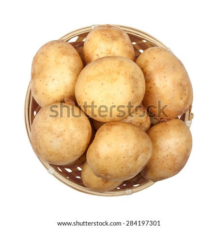 new potatoes in a light basket on an isolated white background - stock photo