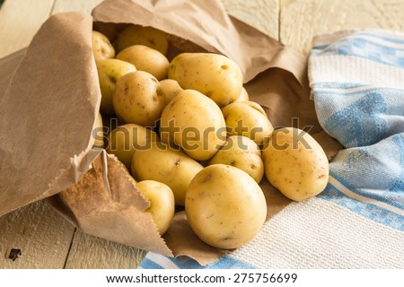 New potatoes on rustic table with brown paper bag - stock photo