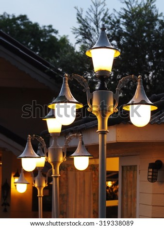 new production vintage retro style design outdoor public street lamp glowing in a park with dark green pine tree and evening sky in the background.  - stock photo