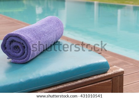 New purple towel on bed pool, towel background, towel concept, towel copy space, towel swimming pool. - stock photo