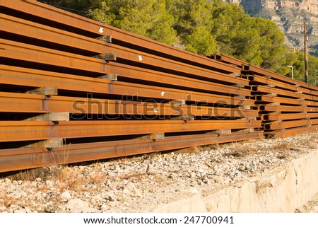 New rails piled up at a railroad construction site - stock photo