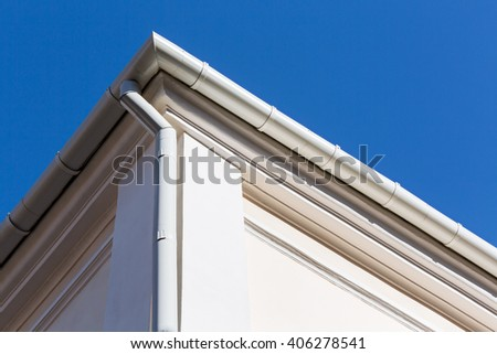 new rain gutter on a home against blue sky - stock photo