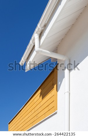 New rain gutter on a home with wooden panel against blue sky - stock photo