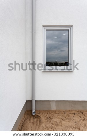 New rain gutter on a white wall with window - stock photo