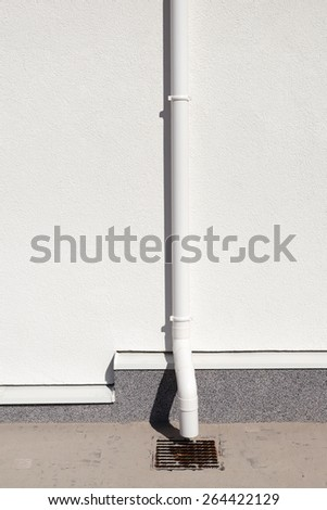 New rain gutter on white wall - stock photo