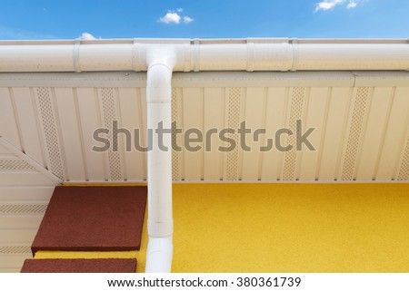 New rain gutter on yellow wall - stock photo