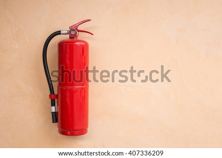 New red fire extinguisher tank on orange wall - stock photo