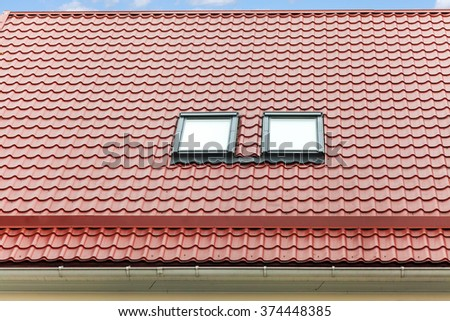 New red metal roof with skylights and rain gutter - stock photo