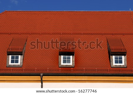 New, red roof in front of a blue sky - stock photo