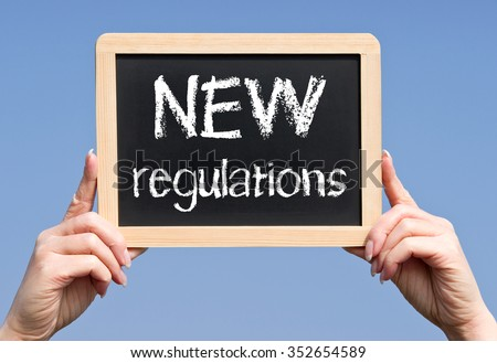 NEW Regulations - female hands holding chalboard with text