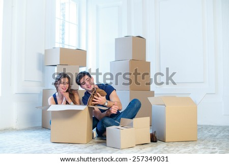 New repair and relocation. Loving couple enjoys a new apartment and keep the box in his hands while young and beautiful couple in love sitting on the couch in an empty apartment among boxes - stock photo