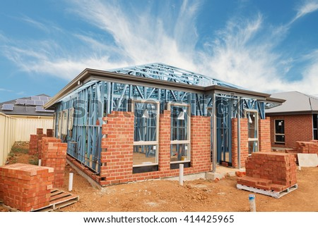 New residential construction brick home with metal framing against a blue sky - stock photo