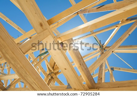 New residential construction home framing against a blue sky and sun - stock photo