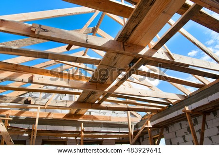 New residential construction home framing against a blue sky. Roofing construction. Wooden construction. Installation of wooden beams at construction the roof truss system of the house
