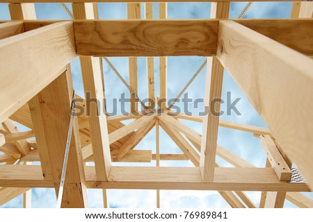 New residential construction home framing against a blue sky.Shallow focus. - stock photo