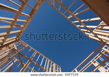 New residential construction home framing against a deep blue sky. - stock photo