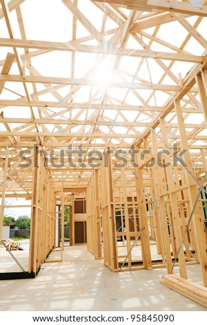 New residential construction home framing against a sunny sky. - stock photo