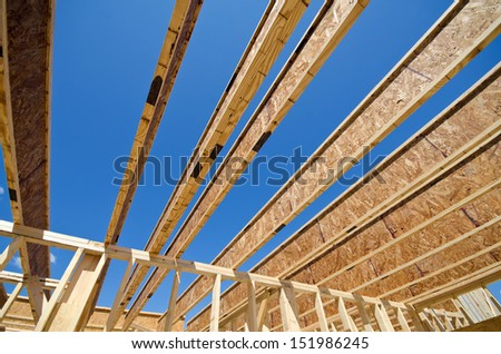 New residential construction home framing against blue sky - stock photo
