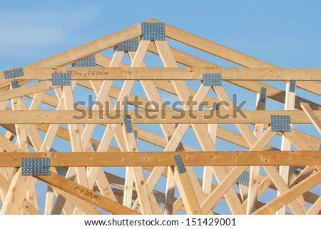 New residential construction home framing over blue sky - stock photo