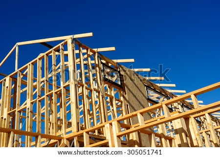New residential construction house framing against a blue sky - stock photo