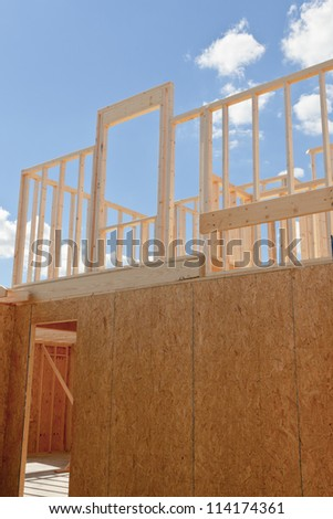 New residential construction house framing against a blue sky. Door to your dream home.