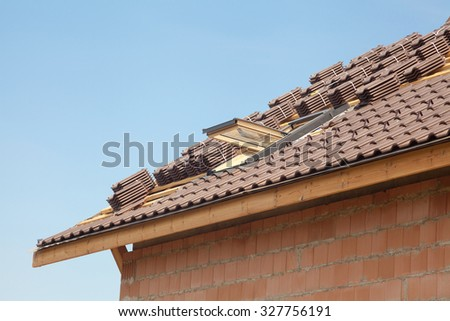 New roof with open skylight, natural red tile against blue sky - stock photo