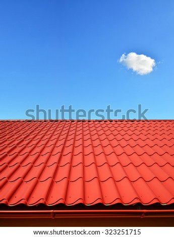 new roof with orange red sheet metal and background of blue sky - stock photo