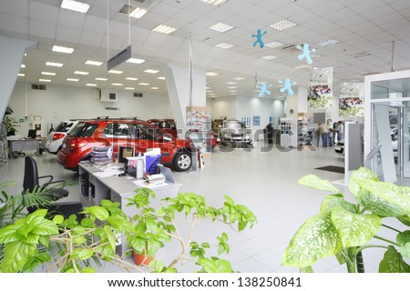 New shine cars stand in big office of shop selling cars near tables with computers. - stock photo