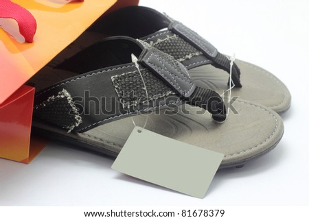 New slipper out of a paper bag on white background