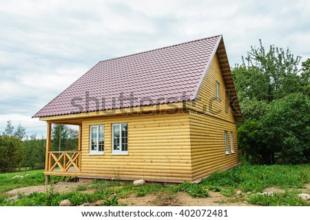 New small wooden house with sundeck, the walls of the yellow blockhouse, the roof covered with red metal tile - stock photo
