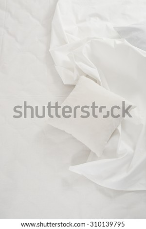 New snow-white bed, pillows and crumpled sheets, white linen cloth, white abstract background.