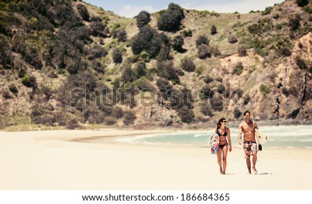NEW SOUTH WALES, AUSTRALIA - DECEMBER 30, 2012: Couple walking with surfboards on Byron Bay beach in New South Wales on December 30, 2012, Australia - stock photo