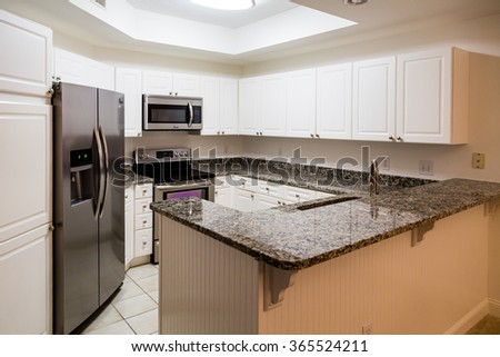 New stainless steel appliances and granite countertops with white wod cabinets - stock photo