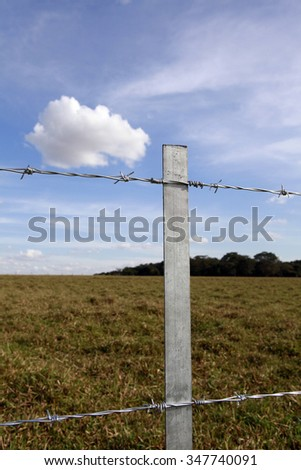 new steel fence in farm with blue sky and clouds in background on countryside in brazil - stock photo