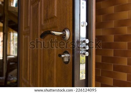 new steel three bolt door lock installed on the wooden front door of a new build