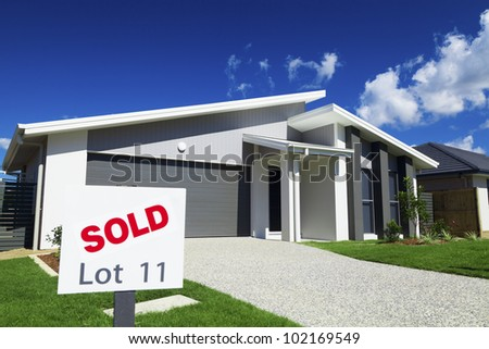 New suburban Australian house with large SOLD sign. - stock photo