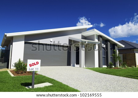 New suburban Australian house with small SOLD sign. - stock photo