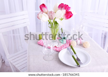 New table and chairs with table settings and spring decorations on light background