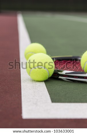 New tennis balls and racket on baseline of court with blurred net in background