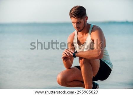 New time. Confident young muscular man checking time on his watches while sitting at the seaside - stock photo