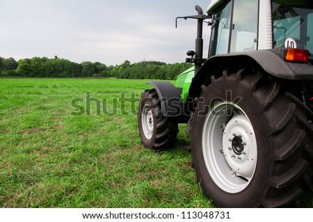 new tractor on a green field - stock photo