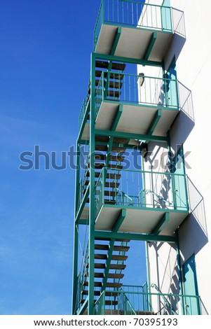 New turquoise green fire escape against bright blue sky - stock photo