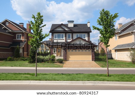 New two-storied brown brick cottage with garage in front of it. - stock photo