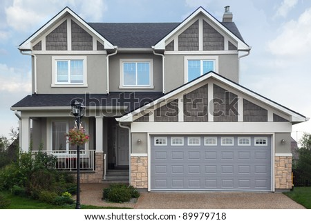 New two-storied gray brick cottage with garage on first floor. - stock photo