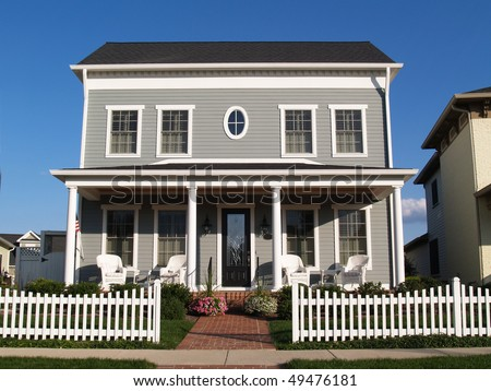 New two story vinyl home built to look like an old historical house with gray vinyl siding and large front porch. - stock photo